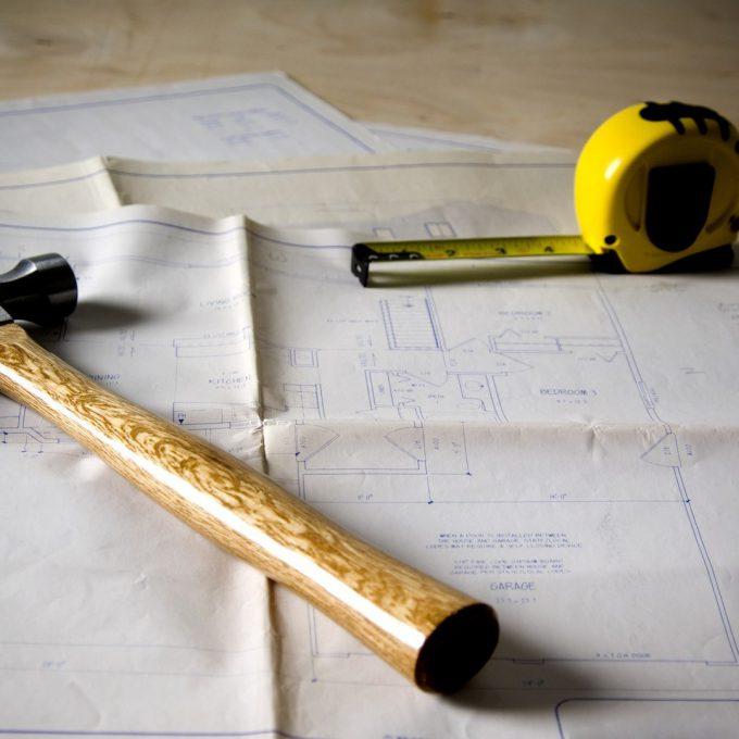 Blueprints, tape measure, hammer